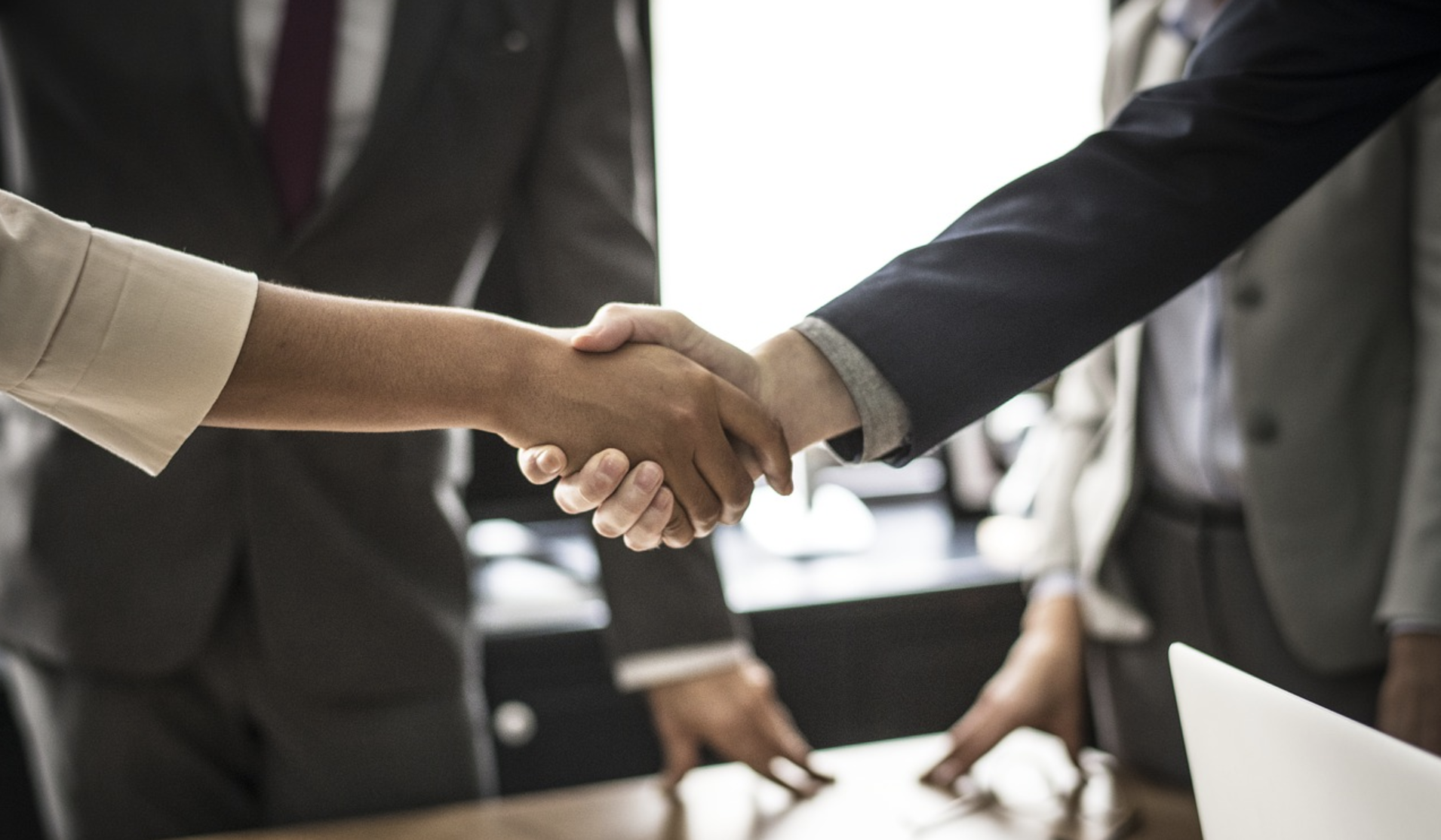 Two people shaking hands in a conference room